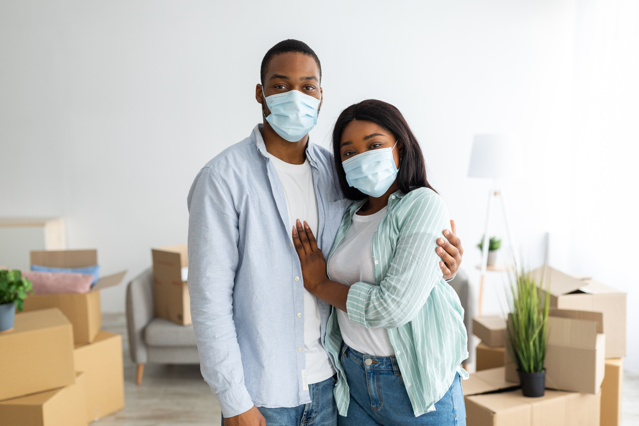 Moving home concept. Sad african american couple in protective masks standing among packed cardboard boxes, moving because of epidemic. Real estate and relocation