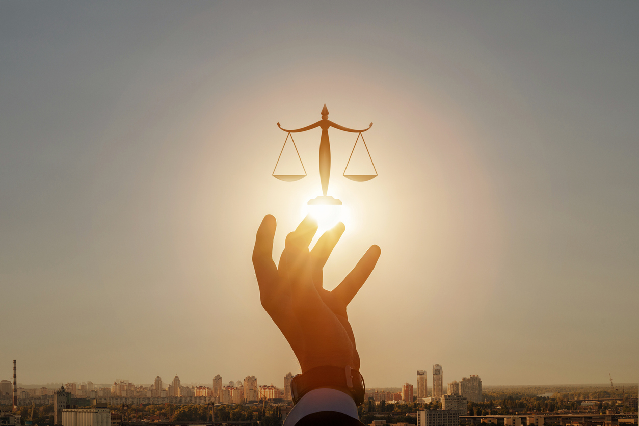 Concepts of justice and jurisdiction in a city.Hand shows Scales of Justice against the backdrop of a sunny city sunset.