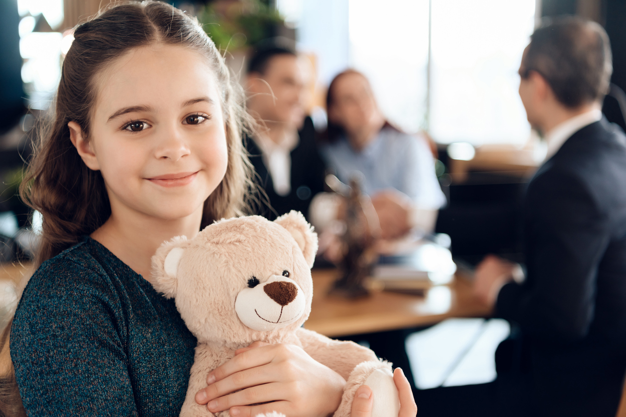 A young girl stands with a teddy bear and smiling at camera. Beautiful girl with parents stands in the office of a lawyer.